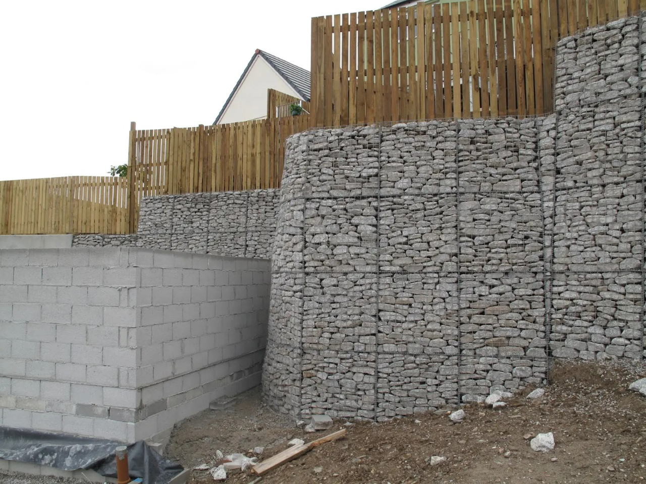 stone wall with wooden fence and building
